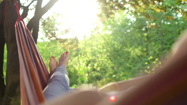 young woman relaxing in a hammock under the trees - taking a break stock videos & royalty-free footage