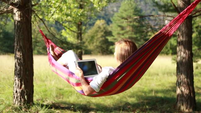 vídeos de stock e filmes b-roll de jovem mulher relaxante na cama usando tablet digital - cama de rede