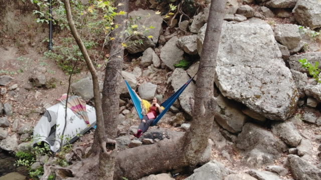 young woman relaxing in a hammock - ozgurdonmaz stock videos and b-roll footage