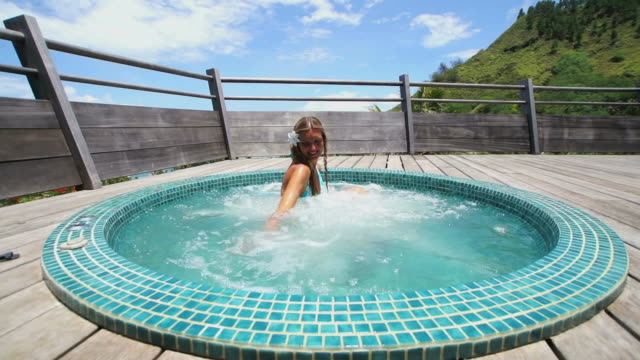 young woman relaxing in an outdoor whirlpool spa - hot tub stock videos and b-roll footage