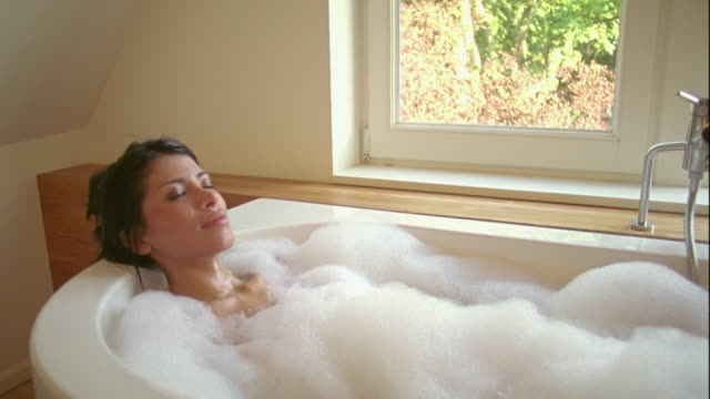 MS, CU, Young woman relaxing in bubble bath, Brussels, Belgium