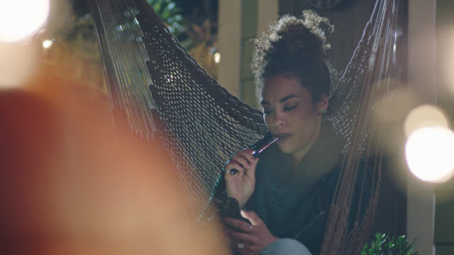 Young woman relaxing in hammock looks at smartphone while vaping.