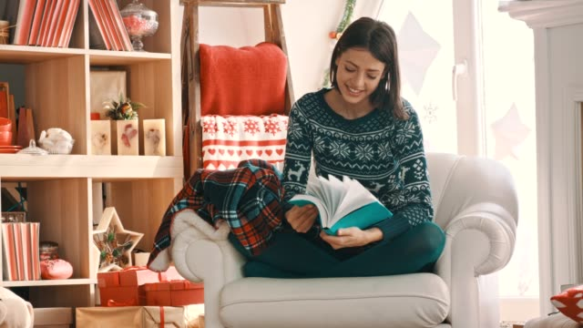 young woman relaxing in her chair and flipping through the book she wants to read - reading book stock videos & royalty-free footage