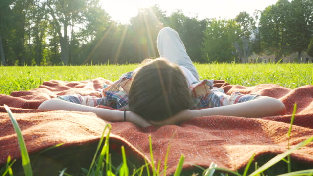 young woman relaxing in nature. - sdraiato video stock e b–roll