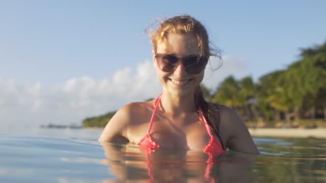 Ung kvinna avkopplande i havet med tropisk strand i bakgrunden