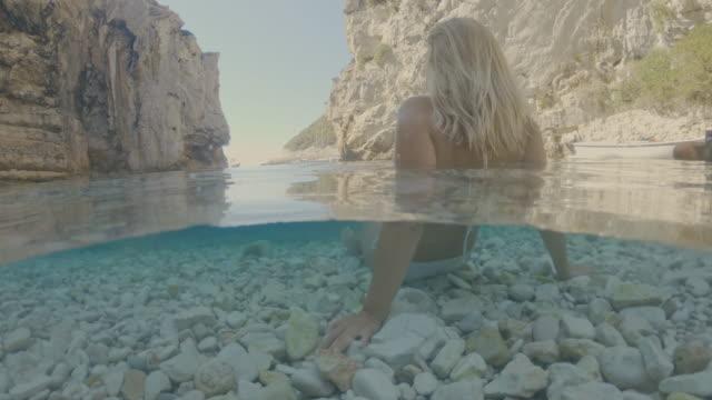 岩の多い海、アドリア海、クロアチアでリラックスしたms若い女性 - 水中カメラ点の映像素材/bロール