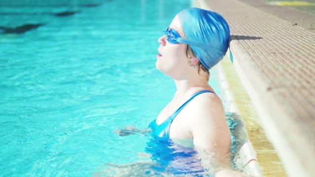 vídeos de stock, filmes e b-roll de young woman relaxing in swimming pool - touca de natação