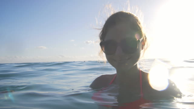 young woman relaxing in the ocean smiling into the camera - bikini stock videos & royalty-free footage