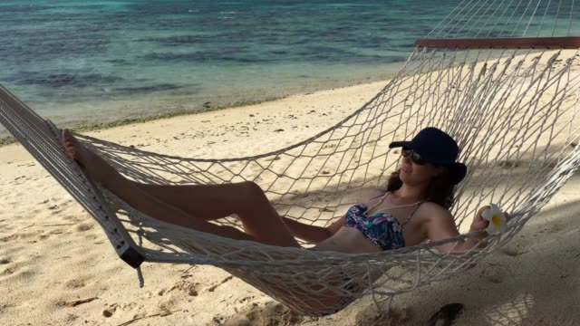 young woman relaxing on a hammock on a tropical pacific island beach - rarotonga stock videos & royalty-free footage
