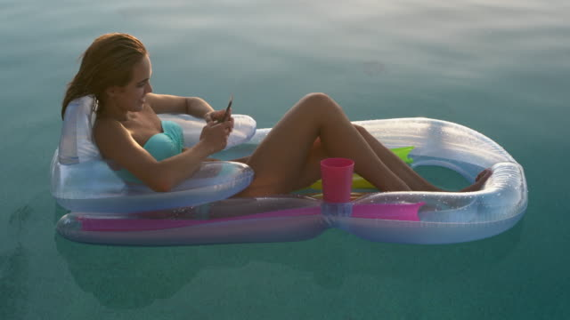 ws young woman relaxing on a inflatable chair in a swimming pool - sunbathing video stock e b–roll