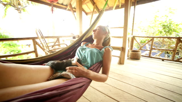 Young woman relaxing on hammock with kitty