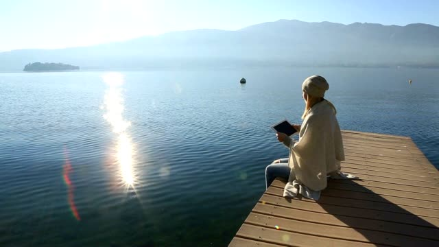 Young woman relaxing on lake pier with digital tablet