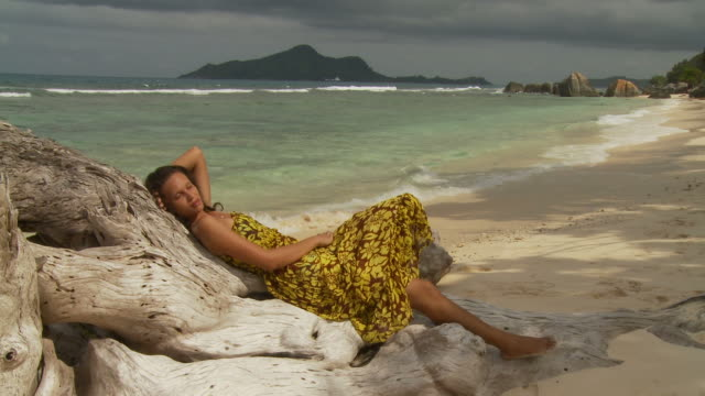 WS Young woman relaxing on log on beach / Seychelles