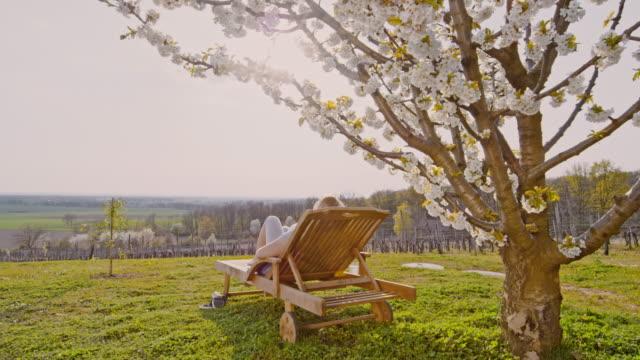 vídeos y material grabado en eventos de stock de ws mujer joven relajante en la silla de salón debajo de árbol de cerezo en colina soleada, idílica - acostado