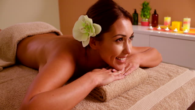 young woman relaxing on massage table at health spa - massage table stock videos & royalty-free footage
