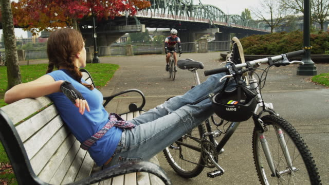 ws young woman relaxing on park bench waving to male cyclist passing by / portland, oregon, usa - see other clips from this shoot 1695 stock videos & royalty-free footage