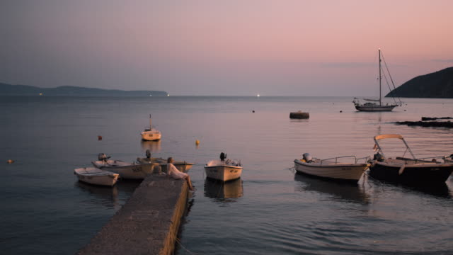 ws young woman relaxing on pier at tranquil dusk harbor,adriatic sea,croatia - moor stock videos & royalty-free footage