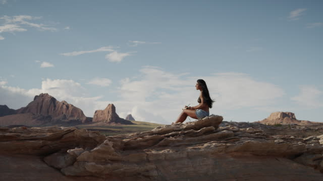 ws ds young woman relaxing on rocks near lake powell / utah, usa - lake powell stock videos and b-roll footage