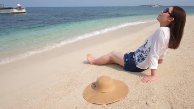 vídeos de stock, filmes e b-roll de jovem mulher relaxante na praia no verão, 4 k (uhd - tomando sol