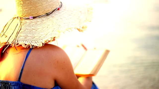 若い女性リラックスしたビーチで本を読んで - 麦わら帽子点の映像素材/bロール