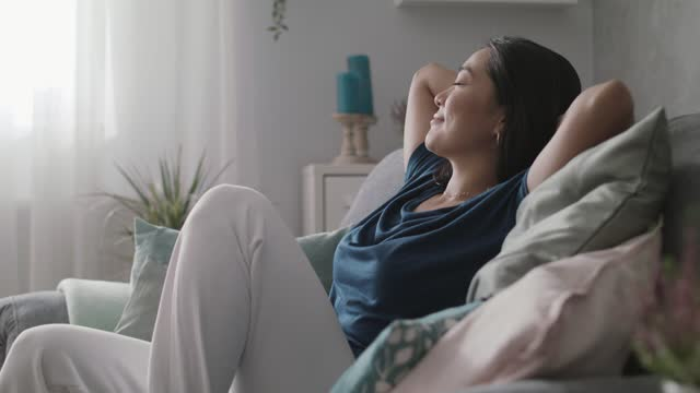 young woman relaxing on the cozy sofa with hands behind her head - hands behind head stock videos & royalty-free footage