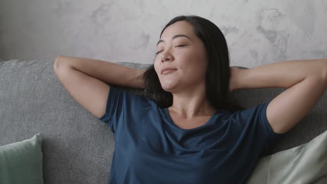 young woman relaxing on the sofa and taking a nap - hands behind head stock videos & royalty-free footage