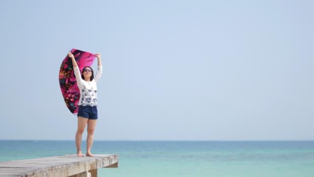 stockvideo's en b-roll-footage met jonge vrouw ontspannen op houten brug op zomertijd op de zee, ontspanning concept - menselijke arm