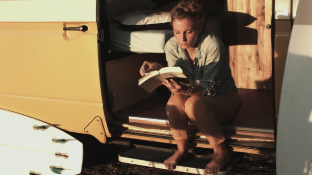 Young woman relaxing, reading book in VW bus with surfboards in campground in the South of France.