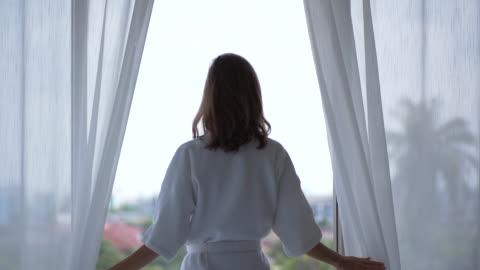 junge frau entspannende zeit öffnen das fenster blick nach draußen - stehen stock-videos und b-roll-filmmaterial