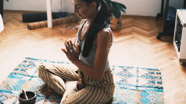 junge frau entspannen beim meditieren zu hause - gebetsposition stock-videos und b-roll-filmmaterial