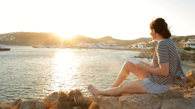 Young woman relaxing while reading a book at sunset.