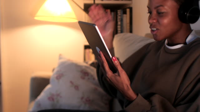 Young woman relaxing with a digital tablet at home.