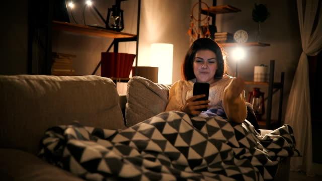 Junge Frau entspannenden auf sofa mit smartphone