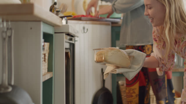 young woman removes a fresh-baked loaf of bread from oven and sets it on kitchen counter - kitchen worktop stock videos & royalty-free footage