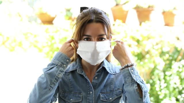 vídeos de stock, filmes e b-roll de jovem removendo uma máscara facial cirúrgica protetora - máscara cirúrgica
