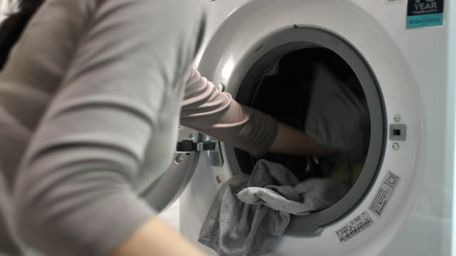 young woman removing clothing clean laundry from the tumble dryer at home - tumble dryer stock videos & royalty-free footage