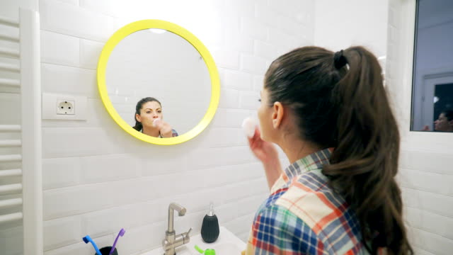Young woman removing make-up in bathroom.