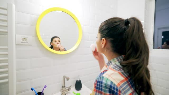 Junge Frau entfernen Make-up im Badezimmer.