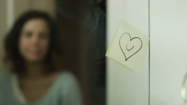 vídeos de stock e filmes b-roll de cu r/f young woman removing post it note with heart from bathroom mirror and smiling/ provo, utah, usa - papel adesivo