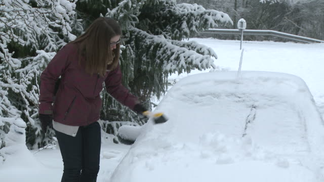 MS Young woman removing snow from car with brush / Saarburg, Rhineland-Palatinate, Germany