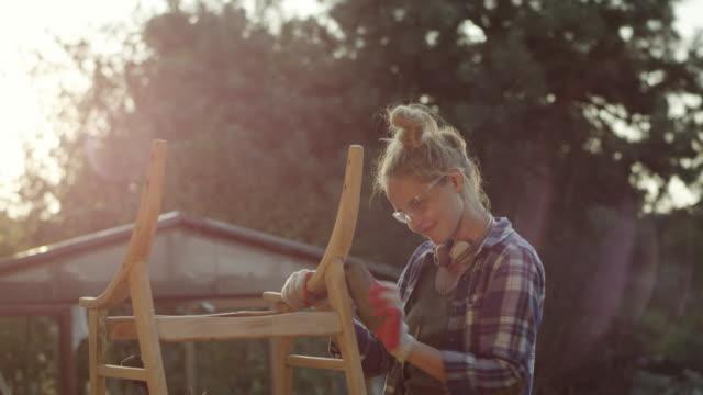 Junge Frau, die Renovierung von alten Möbeln
