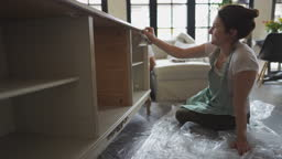 Young woman repairing an old furniture and enjoying at home