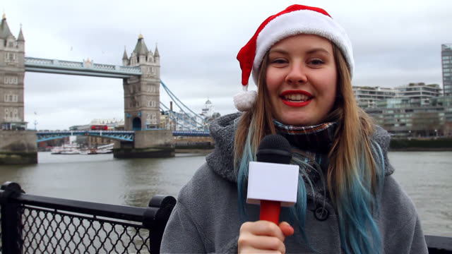 young woman reporter wearing christmas hat and talking on microphone near tower bridge, london, uk - interview stock videos & royalty-free footage