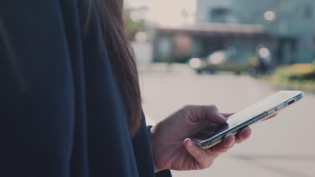vidéos et rushes de jeune femme demandant et uber depuis un téléphone intelligent en attente - questions sociales