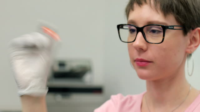 young woman researcher shaking scientific sample in laboratory - scientific sample stock videos & royalty-free footage