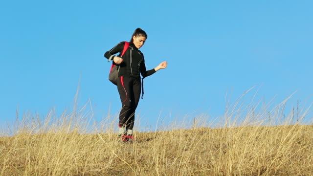 vídeos de stock, filmes e b-roll de jovem mulher descansando depois de uma corrida longa na colina. - a parar