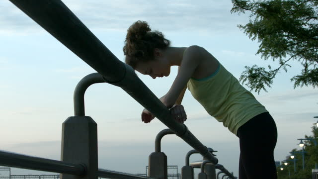 A young woman resting after a run outside in New York City in slow motion