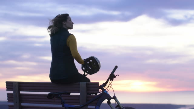 stockvideo's en b-roll-footage met ws young woman resting after mountain biking - hoofddeksel
