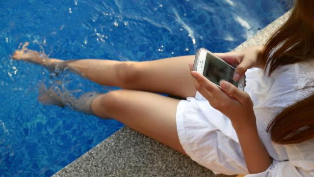 Jonge vrouw rusten en het gebruik van smartphone aan het zwembad
