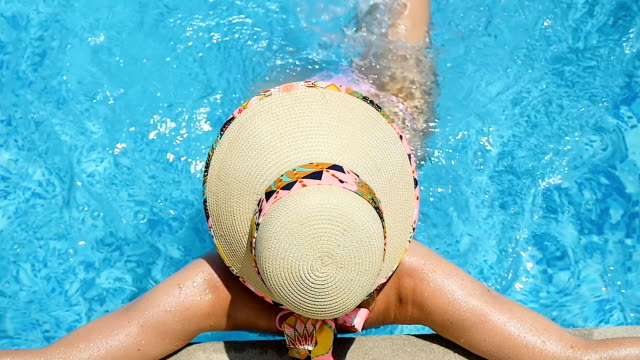 young woman resting in resort pool - straw hat stock videos and b-roll footage